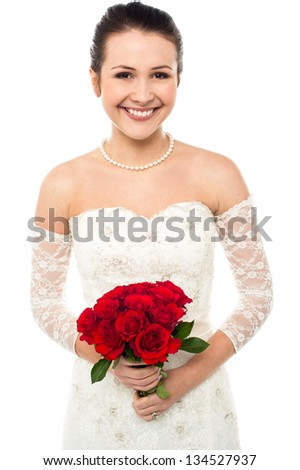 Gorgeous young bride holding a rose bouquet smiling at the camera. - stock photo
