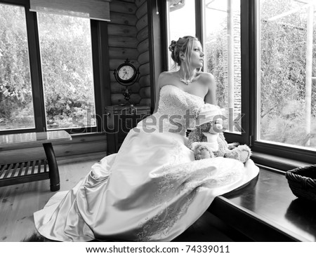 Gorgeous young bride looking out of the window - stock photo