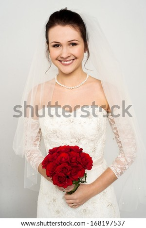 Gorgeous young bride with a rose bouquet against gray - stock photo