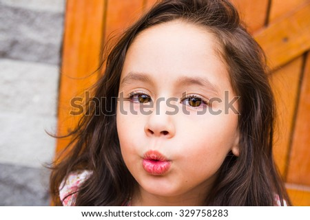 Gorgeous young brunette girl closeup headshot posing for camera, wooden door background. - stock photo