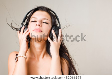 Gorgeous  young brunette immersed in music wearing headphones, with eyes closed - stock photo
