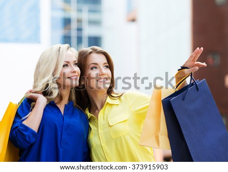 Gorgeous young brunette with beautiful young blond pointing at showcase of mall. - stock photo