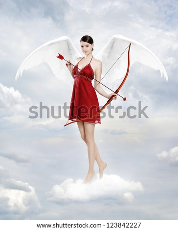 Gorgeous young brunette woman as cupid angel in clouds with white wings, bow and arrow - stock photo