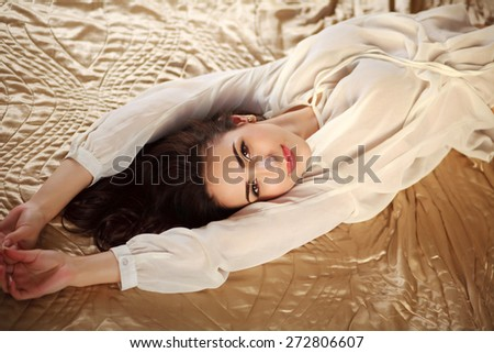 Gorgeous young brunette woman relaxing lying in lingerie on bed and sensually smiling - stock photo