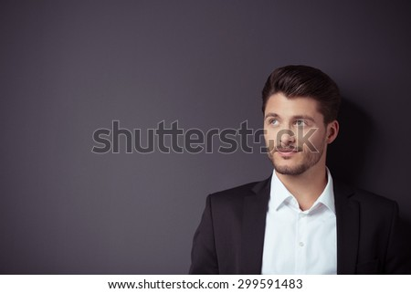 Gorgeous Young Businessman Looking Up Against Dark Gray Wall Background with Copy Space on the Left. - stock photo