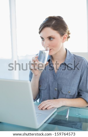 Gorgeous young businesswoman drinking a glass of water sitting at her desk in front of her laptop - stock photo