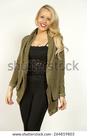 Gorgeous young happy female blonde with wavy hair in a studio setting while wearing a hip green top and black outfit under on a white background. - stock photo