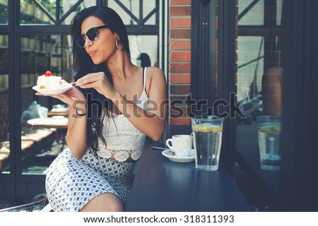 Gorgeous young latin woman dressed in stylish clothes and sunglasses sitting in a sidewalk cafe in summer while enjoying gentle sweet dessert and fresh water with lemon, female tourist eat sweet cake - stock photo