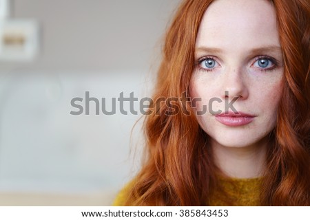 Gorgeous young redhead woman with long coppery hair and blue eyes looking at the camera, close up head shot with copy space - stock photo