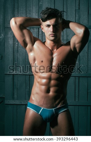 Gorgeous young sexy muscular bodybuilder man with cool pectorals  abdominal muscles and biceps looking straight wearing in blue underwear posing with hands behind head on dark background, vertical - stock photo