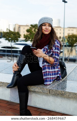 Gorgeous young woman using her smart phone while looking to the side outdoors, beautiful female student holding cellphone while sitting on the bench, hipster girl looking to someone in the park - stock photo