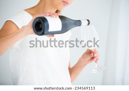 Gorgeous young woman with a glass of wine, smelling the lovely drink, savouring   every sip (shallow DOF; color toned image) - stock photo