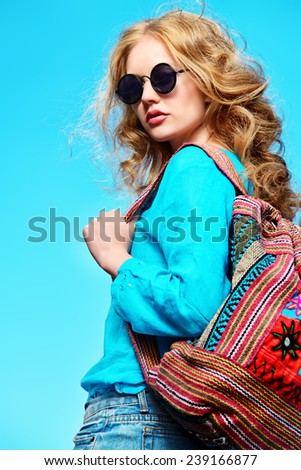 Gorgeous young woman with beautiful wavy hair wearing casual blouse and jeans shorts posing outdoor. Fashion shot. - stock photo