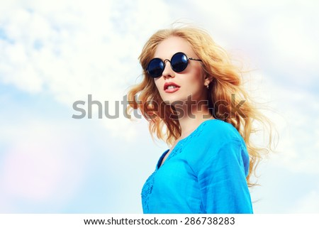 Gorgeous young woman with beautiful wavy hair wearing casual blouse and sunglasses posing outdoor. Fashion shot. - stock photo