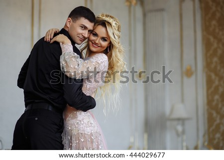 Gorgeous young woman with perfect makeup and hair style in luxury dress with a man in black clothes in interior - stock photo