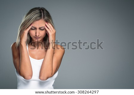 Gorgeous young woman with severe headache/migraine/depression symptoms (color toned image) - stock photo