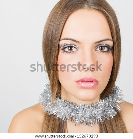Gorgeous young woman with silver decoration and makeup - stock photo