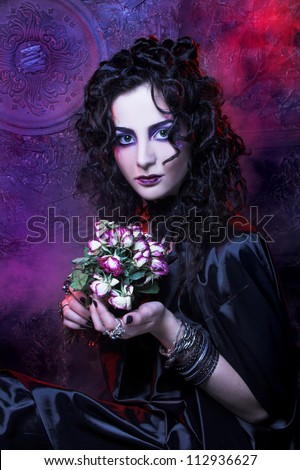 Gorgon. Young woman with dry roses and in dark dramatic image. - stock photo
