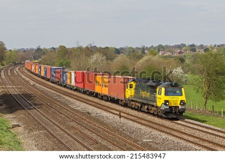 GORING, UK - APRIL 9: An FLT operated intermodal train passes Berkshire with an eastbound freight train on April 9, 2014 in Goring. FLT was founded in 1995 and has an operating revenue of £360Mn - stock photo