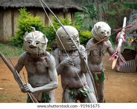 GOROKA, PAPUA, NEW GUINEA - SEPTEMBER 16: Mudmen warriors clasp their weapons at Goroka Tribal Festival  in Goroka, Papua New Guinea on September 16, 2011 - stock photo