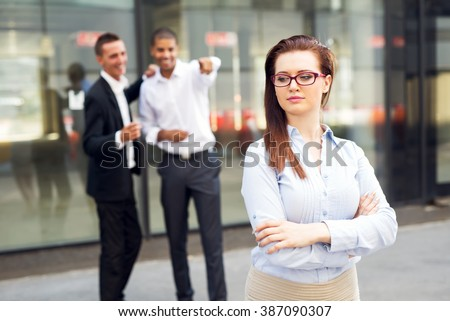 Gossip colleagues in front of their office,beautiful businesswoman portrait and gossip out of focus in background. - stock photo