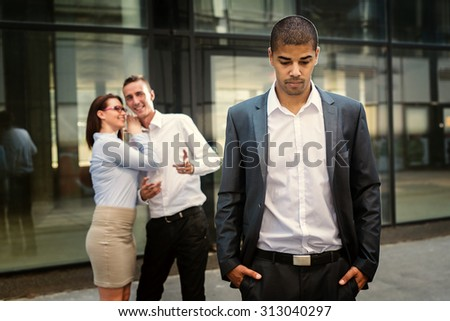 Gossip colleagues in front of their office, handsome businessman portrait and gossip out of focus in background. - stock photo