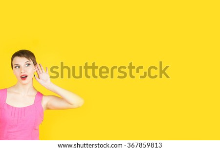 Gossip concept. Colorful studio portrait of pretty young woman with palm near her ear. - stock photo