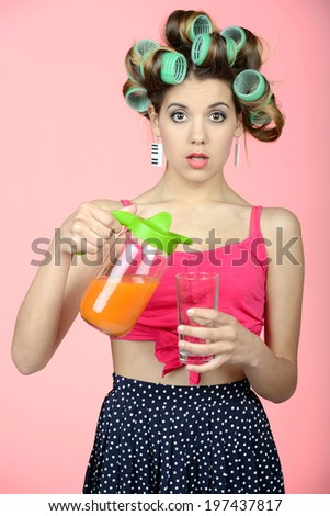 Got Juice? Sexy young housewife pouring some orange juice into the glass - stock photo