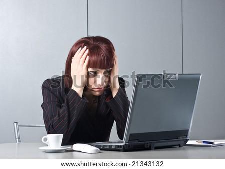 Got tired Beautiful businesswomen behind a desktop and a laptop - stock photo