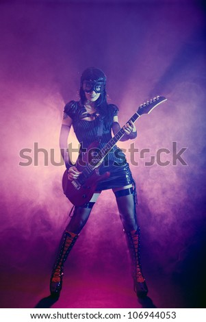 Goth girl in goggles plays guitar on the stage - stock photo