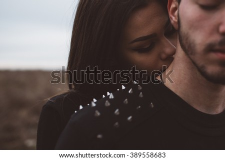 Goth girl kisses her boyfriend on the neck  - stock photo