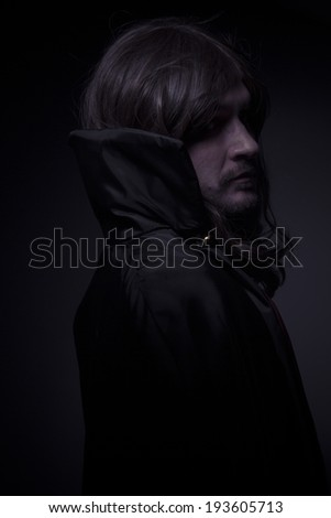 Goth, man with long hair and black coat - stock photo