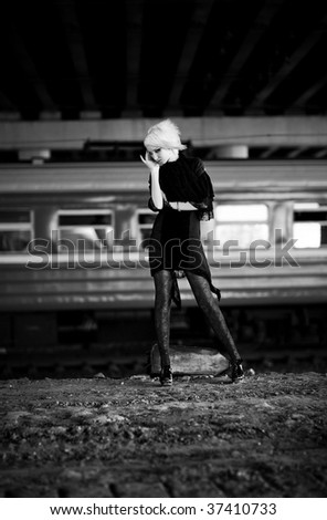 Goth woman in industrial zone. On moving train background. - stock photo