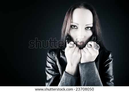 Goth woman portrait. On dark background. - stock photo