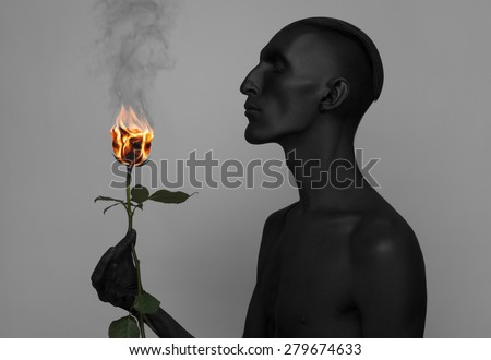 Gothic and Halloween theme: a man with black skin holding a burning rose, black death isolated on a gray background in studio - stock photo