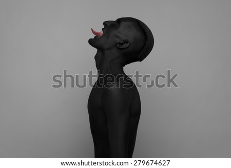 Gothic and Halloween theme: a man with black skin is isolated on a gray background in the studio, the Black Death body art - stock photo