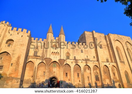 Gothic architecture of the large Papal Palace (Palais des Papes) at evening, Avignon, Provence, France - stock photo