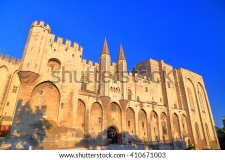 Gothic building of the Papal Palace (Palais des Papes) illuminated at sunset, Avignon, Provence, France - stock photo