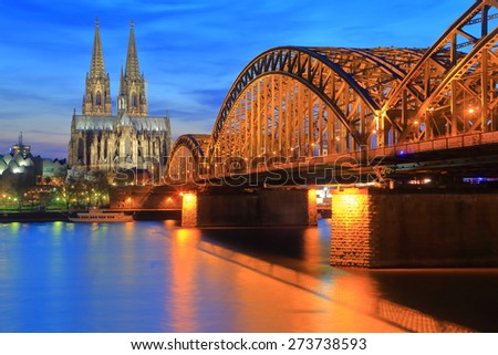 Gothic Cathedral and iron bridge across Rhine river at sunset, Cologne, Germany - stock photo