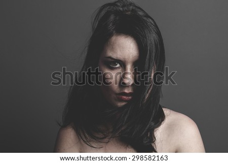 gothic dark woman with large black cloth on gray background, Sadness - stock photo