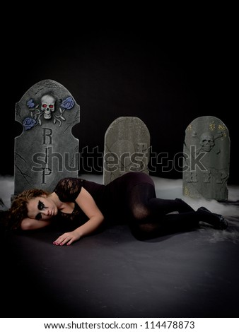 Gothic girl laying in graveyard - stock photo