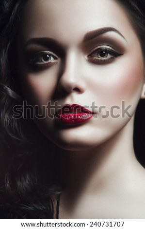 Gothic portrait of young green-eyed lady with black curles, black wings and brown smoky eyes and bardic lipstick looking at you on black background - stock photo