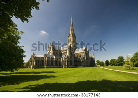 Gothic Salisbury Cathedral viewed across the green park - stock photo