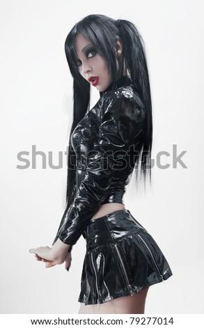 Gothic studio portrait of brunette sexy woman in black vinyl costume - stock photo