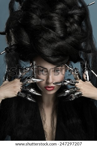 Gothic style shot of a woman with claw rings touching face - stock photo