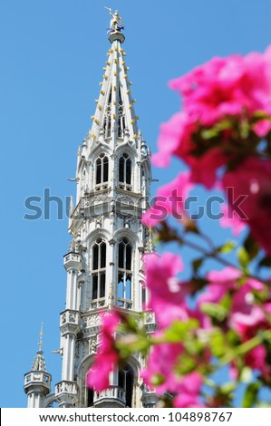 Gothic tower on Grand place in Brussels behind flowers - stock photo