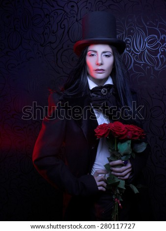 Gothic Valentine. Romantic portrait of young woman in gothic man image posing with red roses. - stock photo