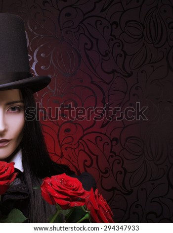 Gothic Valentine. Romantic portrait of young woman in gothic man image posing with red roses - stock photo