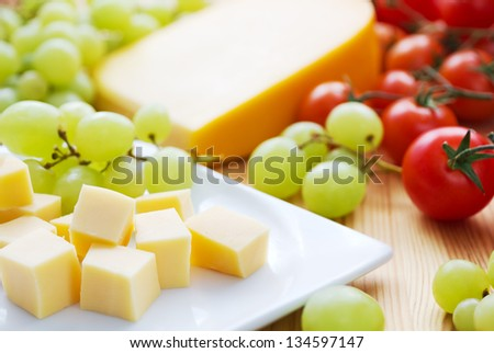 Gouda cheese snack with grapes and tomatoes - stock photo