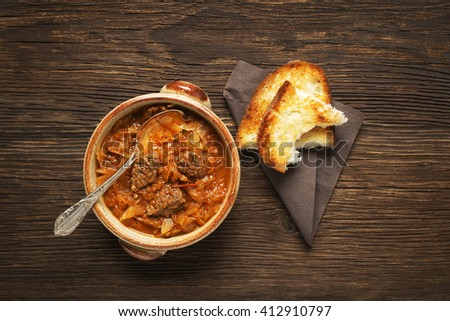Goulash cabbage with beef on wooden background. - stock photo